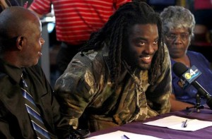 Alex Collins holds a news conference after signing his letter of intent to play for Arkansas on Thursday. He's flanked by his father, Johnny Collins, and grandmother, Betty Collins. (Mike Stocker / McClatchy-Tribune / February 7, 2013)