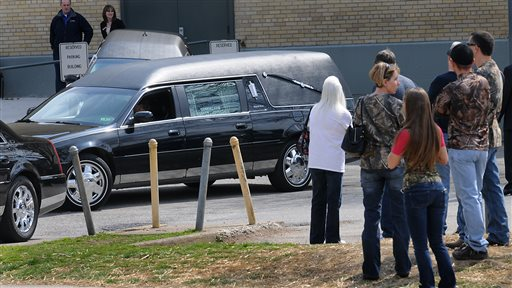 """A hearse leaves the Municipal Auditorium in Charleston, W.Va. after a joint funeral for """"Buckwild"""" star Shain Gandee and his uncle David Gandee Sunday afternoon, April 7, 2013. Gandee, his 48-year-old uncle, David Gandee, and 27-year-old friend Donald Robert Myers were found dead April 1 in a sport utility vehicle that was partially submerged in a deep mud pit near Sissonville. (AP Photo/The Charleston Gazette, Kenny Kemp)"""