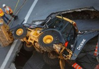 A backhoe fell victim to an 8 metre by 5 metre sinkhole that opened unexpectedly at the intersection of Guy and Saint-Catherine streets in downtown Montreal. The streets gave way at about 9 a.m. on Aug. 5. (Christine Muschi/Reuters)