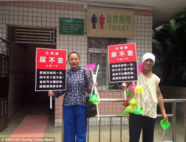 Take aim: Two Chinese women sell the Pee Straight invention outside a public toilet in the city of Shenzhen