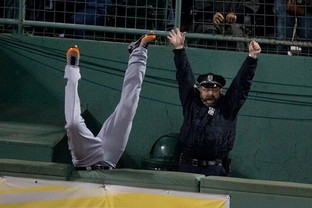 Boston police officer Steve Horgan lifts his arms in triumph as Torii Hunter of the Detroit Tigers tries and fails to catch a grand slam hit by David Ortiz of the Boston Red Sox in the eighth inning of Game Two of the American League Championship Series at Fenway Park on Oct. 13 in Boston.