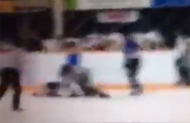 A still image taken from YouTube shows a boy down on the ice after an official intervened in the fight. Photograph by: Alex Pieper , YouTube