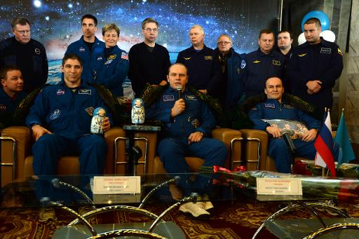 L-R: wearing traditional Kazakh costumes US astronaut Michael Hopkins sits together with Russia's cosmonauts Oleg Kotov and Sergey Ryazansky, as they attend a press conference in Karaganda, Kazakhstan, on March 11, 2014 (Pool/AFP, Vasily Maximov)