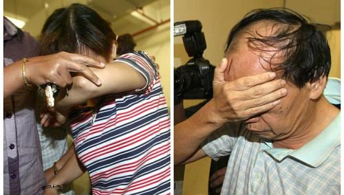 Malaysians Teoh Ching Yen and Fong Kong Meng covering their faces while being taken to court, on June 15, 2011. The couple was sentenced to death by hanging by the High Court on Thursday, March 6, 2014, for murdering their Indonesian maid, Bernama news agency reported. -- FILE PHOTO: CHINA PRESS
