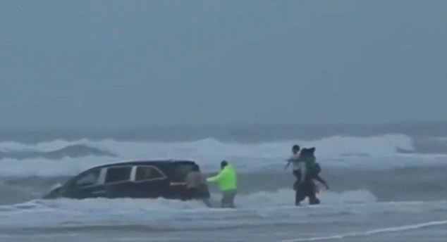 Rescuers wade out to the stricken minivan after it turned sharply and drove into the ocean