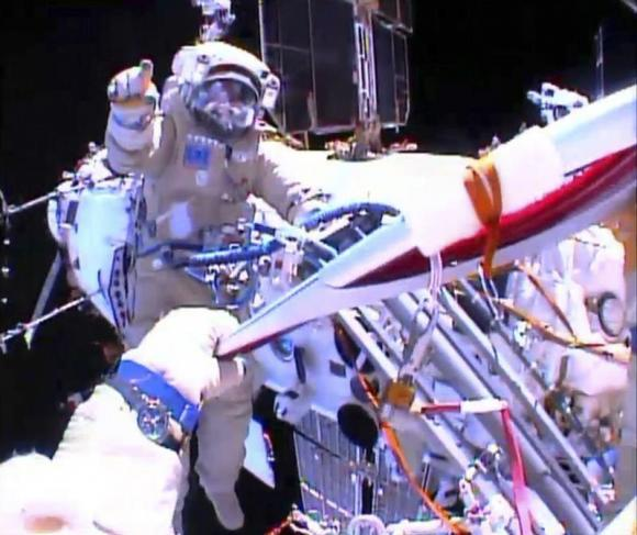 Russian astronaut Oleg Kotov holds an Olympic torch as he takes it on a spacewalk as Russian astronaut Sergei Ryazansky gives instructions outside the International Space Station in this still image taken from video courtesy of NASA TV, November 9, 2013. CREDIT: REUTERS/NASA TV/HANDOUT VIA REUTERS
