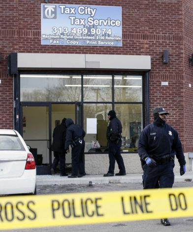 Detroit Police Officers check out the scene after a shooting injuring four people at a tax preparation business in Detroit, Friday, Feb. 28, 2014. Deputy Police Chief Rodney Johnson said a woman became upset when her tax refund wasn't ready Friday and started scuffling with the guard. Johnson said the man with her pulled a gun and started shooting. DETROIT NEWS OUT; ; MANDATORY CREDIT Photo: Jarrad Henderson, AP