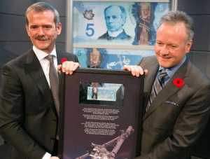 Astronaut Chris Hadfield, left, presents Bank of Canada governor Stephen Poloz with the $5 bill he took into space at a ceremony to officially issue the new $5 polymer note, which features the robotic Canadarm2 and Dextre on Nov. 7, 2013, in Longueuil, Que. (Ryan Remiorz/The Canadian Press)