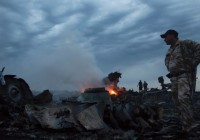 People walk amongst the debris at the crash site of a passenger plane near the village of Grabovo, Ukraine, on Thursday. Officials in Amsterdam, where the flight to Kuala Lampur originated, said one Canadian was among 295 people on the flight. (Dmitry Lovetsky/Associated Press)
