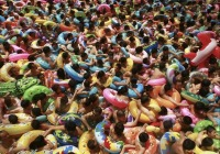 """Holidaymakers, most with swimming rings, crowd in a salty swimming pool, locally known as """"China's Dead Sea,'' as they wait for man-made waves coming to them during a hot summer day in Daying county in southwest China's Sichuan province. (AP Photo)"""