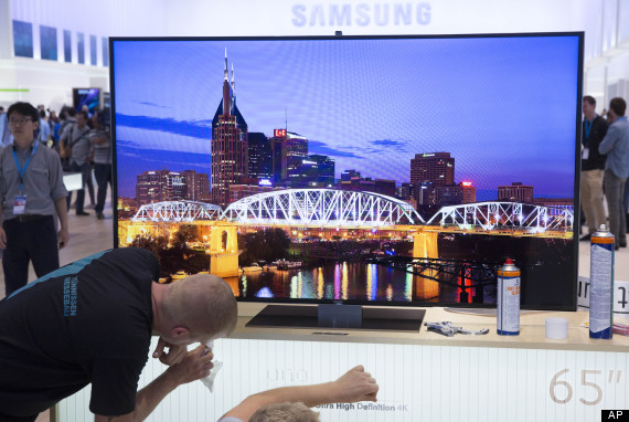 Workers prepare a 65 inch Ultra High Definition 4K television screen for display on the Samsung booth at IFA, one of the world's largest trade fairs for consumer electronics and electrical home appliances, in Berlin, Germany, Thursday, Sept. 5, 2013. IFA will take place on the Berlin Exhibition Grounds from Sept 6 to 11, 2013. (AP Photo/Gero Breloer)