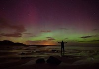 In this photo taken late Thursday Feb. 27, 2014, A man poses standing on a rock looking at the aurora borealis, or northern lights, illuminating the night sky at Embleton Bay in Northumberland, England, Thursday Feb. 27, 2014.