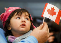 A young Syrian refugee looks up as her father holds her and a Canadian flag at the as they arrive at Pearson Toronto International Airport in Mississauga, Ontario, December 18, 2015.    REUTERS/Mark Blinch       TPX IMAGES OF THE DAY
